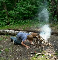 boy kindles bonfire in the deciduous forest