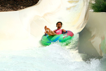 Girl having fun sliding down the waterslide in waterpark