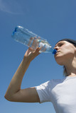 sporty woman have water from bottle over blue sky poster