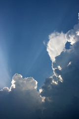 Sun behind clouds in the blue sky before a thunderstorm