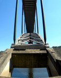 Detail of a bridge with metal arch and heavy pillars poster