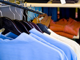 A close up on mens shirts on the rack in a store. poster