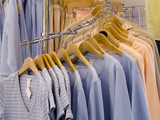 A close up on womans shirts on the rack in a store. poster