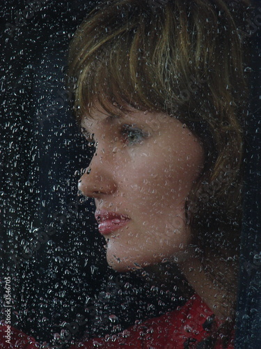Girl looks thru waterdropped widow glass 5