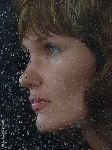 Girl looks thru waterdropped widow glass 4