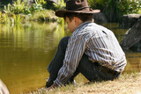 A child sits quietly by the edge of a small pond billabong poster