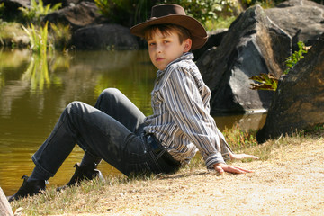 A boy sitting on banks of a  river inlet in outback Australia.