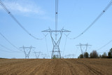 Ploughed land ready for cultivation and electricity pylons. poster