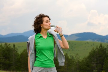 Pretty lady drinking water after exercising