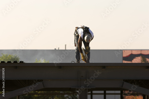 Construction welder on the roof of a building