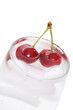 Colorful cherries in a glass of ice water over white