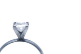 A close-up of a white gold engagement ring. poster