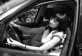 Beautiful brunette in the automobile. b/w poster