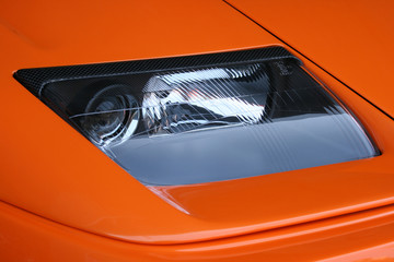 Headlamp on orange car