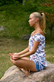 pretty blonde girl meditating on the stone in nature scenic poster