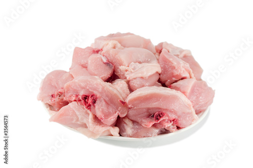 raw sliced chicken on plate isolated on white