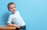 Little boy with smile, leaning on a desk looking forward poster