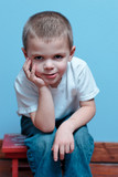 Little boy with smile, sitting on a stool looking forward poster