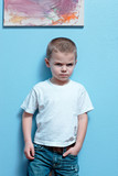 Little boy mad look on face standing against a wall poster