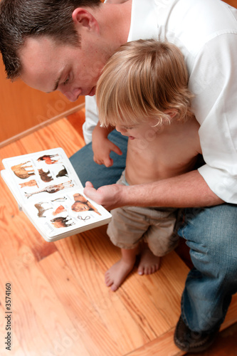 Father looking at a childs book with his son.