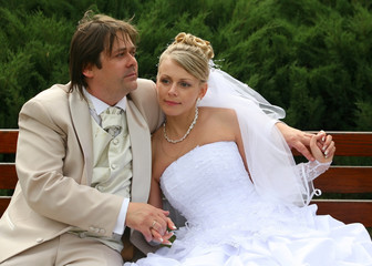 Recently married pair sits on a bench in park