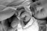 newborn girl holding on to her daddy's finger while sleeping