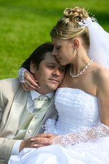 Recently married pair sits on a grass in park