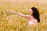 The happy young woman on a yellow field of wheat poster