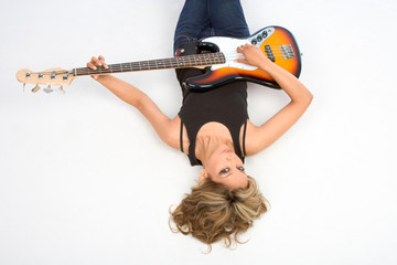 Latina Girl laying on the floor with bass guitar