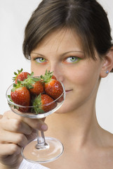 portrait of a young brunette with strawberry in a glass