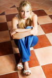 blond woman sitting on a mosaic floor in empty room poster