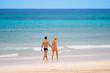 junges paar in badekleidung geht am strand entlang
