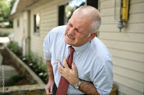 mature businessman clutching his chest