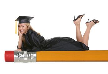 A beautiful woman graduate laying on pencil
