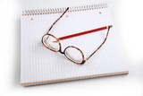 Pictures of glasses resting on a notepad,  poster