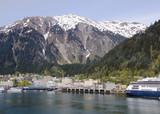 Juneau, Alaska at the base of snow-covered mountains poster