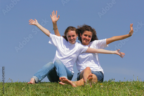 Two teen girls wave hands against a blue sky