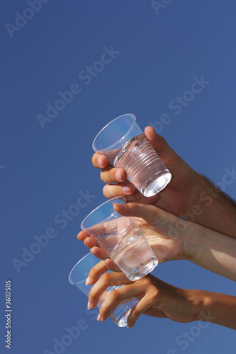 Glasses with transparent beverage in hands against a blue sky