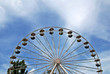 ferris wheel with trees on a blue sky