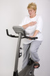 woman on excercise bike clutching chest