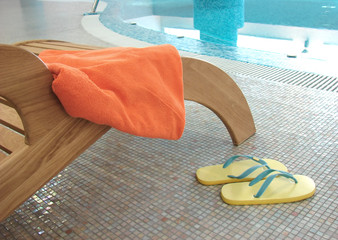 sunbed with orange towel on the armrest and yellow sandals near