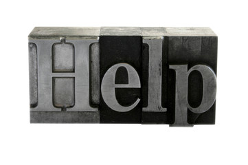 old, inkstained metal type letters form the word 'Help'