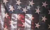 backlit old American flag showing stars over stars