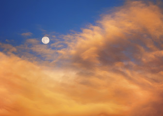 Beautiful yellow and orange sunrise clouds with full moon