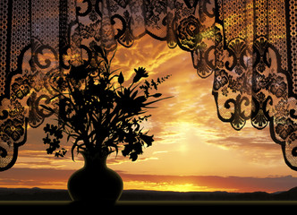 Window view to beautiful sunset with flowers and lace curtain