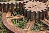 old cogs and gears lay rusting in the grass poster
