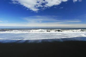 waves crashing on a sandy black beach , deep blue sky