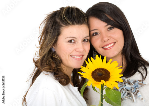beautiful sisters portrait with a yellow sunflower - isolated