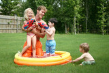 Boys and girl play with dad in the kiddie pool with water guns poster