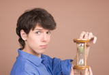 Young businessman with sand-glass  isolated on beige poster